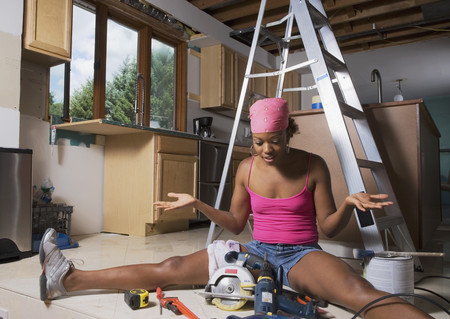 power tools: African woman shrugging shoulders at power tools