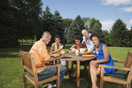 jeopardizing: Multi-ethnic friends eating outdoors LANG_EVOIMAGES