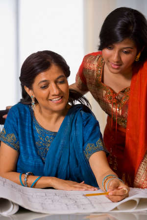 three generation: Indian businesswomen looking at blueprints LANG_EVOIMAGES