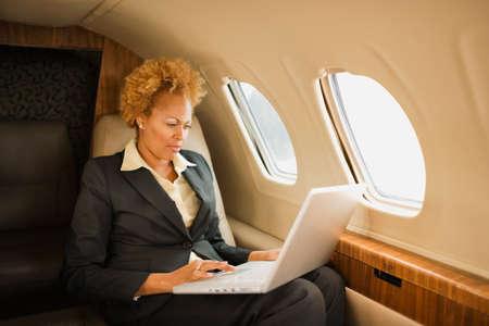 mujeres sentadas: Empresaria afroamericana en avi�n LANG_EVOIMAGES