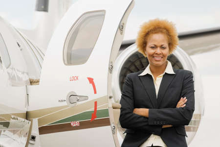 ostentatious: African American businesswoman next to airplane LANG_EVOIMAGES