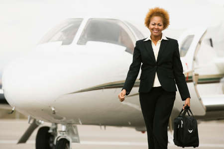 one mid adult woman only: African American businesswoman walking away from airplane