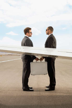 Multi-ethnic businessmen exchanging briefcase Stock Photo