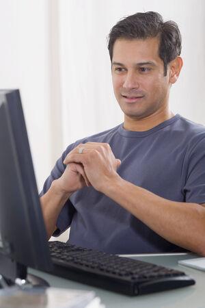 fruit eater: Hispanic man looking at computer LANG_EVOIMAGES