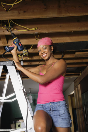 inner strength: African woman on ladder using drill