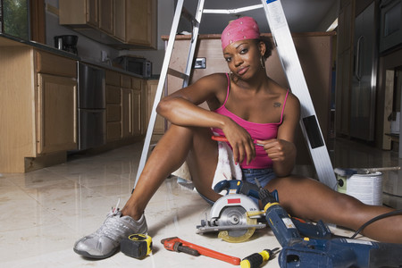 power tools: African woman on floor with power tools LANG_EVOIMAGES