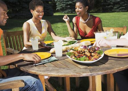 mujeres sentadas: Los amigos del afroamericano que comen al aire libre