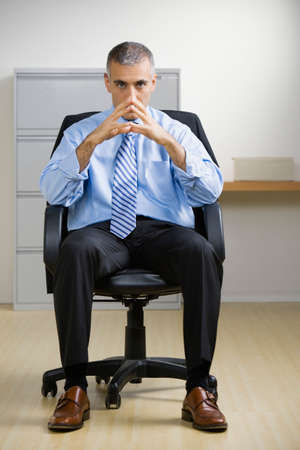 wearying: Middle Eastern businessman sitting in chair