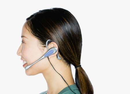 handsfree device: Asian woman wearing hands-free device LANG_EVOIMAGES