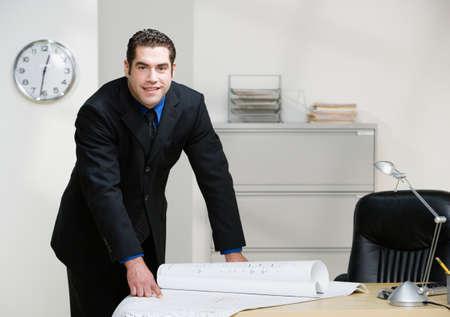athletic gear: Hispanic businessman leaning on desk