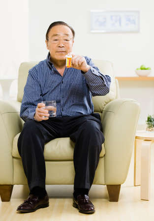 solicitous: Senior Asian man looking at medication LANG_EVOIMAGES