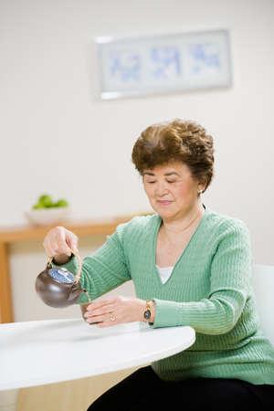 grampa: Senior Asian woman pouring tea