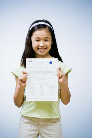 solicitous: Asian girl holding up school paper LANG_EVOIMAGES