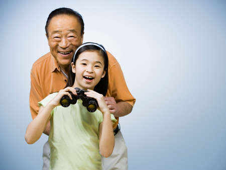 gramma: Asian grandfather and granddaughter holding binoculars