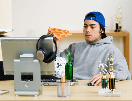 negative area: Mixed Race man eating pizza at computer desk