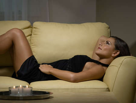 couple on couch: Woman in evening gown laying on sofa LANG_EVOIMAGES