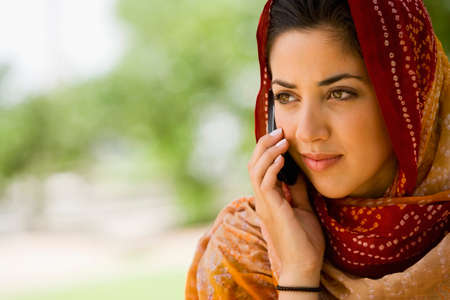 telecommuter: Middle Eastern woman talking on cell phone