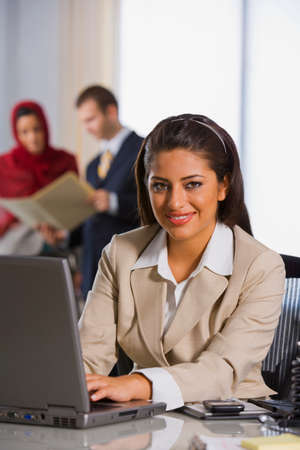 relishing: Indian businesswoman typing on laptop