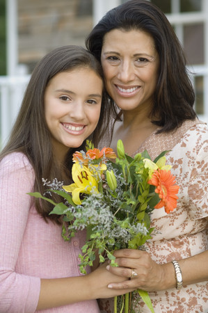 three generations of women: Hispanic mother and daughter holding flowers