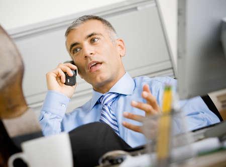 hombre sentado: Hombre de negocios de Oriente Medio que habla en el tel�fono LANG_EVOIMAGES
