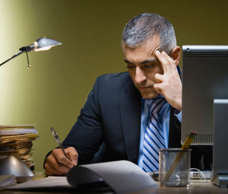 middle eastern: Middle Eastern businessman writing at desk