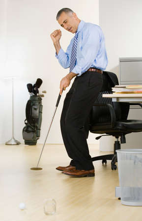 wearying: Middle Eastern businessman hitting golf ball in office