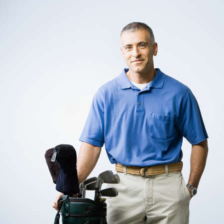 over worked: Middle Eastern man next to golf bag