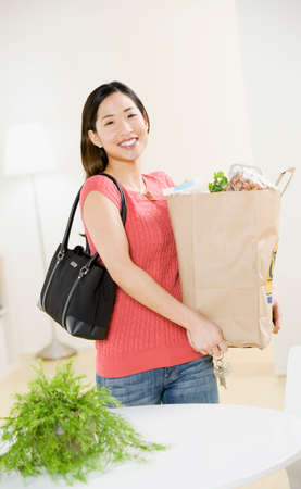 rooting: Asian woman carrying grocery bag