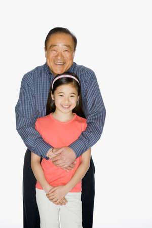 three generations of women: Asian grandfather hugging granddaughter