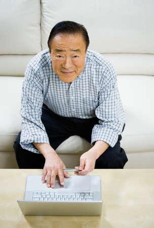 gramma: Senior Asian man shopping online LANG_EVOIMAGES