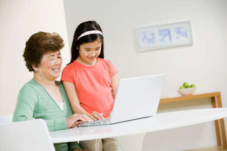 attentiveness: Asian grandmother and granddaughter looking at laptop LANG_EVOIMAGES