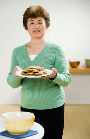 gramma: Senior Asian woman holding plate of cookies LANG_EVOIMAGES