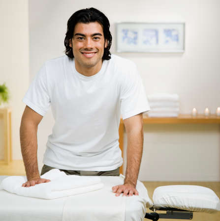 solicitous: Mixed Race man next to massage table