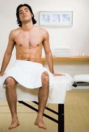 massage  table: Mixed Race man sitting on massage table