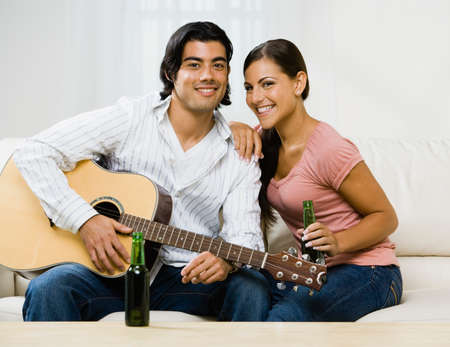 playing on divan: Multi-ethnic couple with guitar LANG_EVOIMAGES