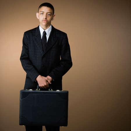 Mixed Race teenage boy holding briefcase
