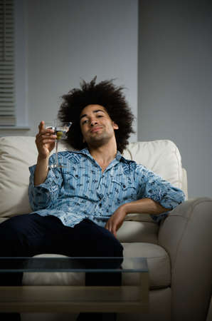bedcover: Mixed Race man with cocktail on sofa LANG_EVOIMAGES