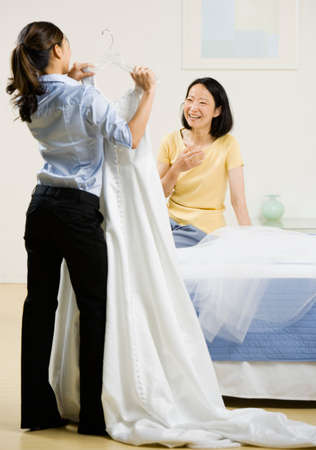 Asian woman showing wedding dress to mother