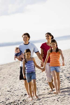 Multi-ethnic family walking on beach LANG_EVOIMAGES