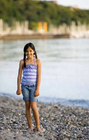 Mixed Race girl standing on rocky beach Stock Photo