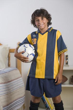 Mixed Race boy holding soccer ball