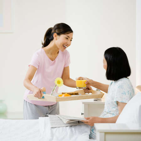mid life: Asian woman bringing mother breakfast in bed LANG_EVOIMAGES