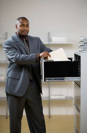 adult  body writing: African American businessman looking in file cabinet