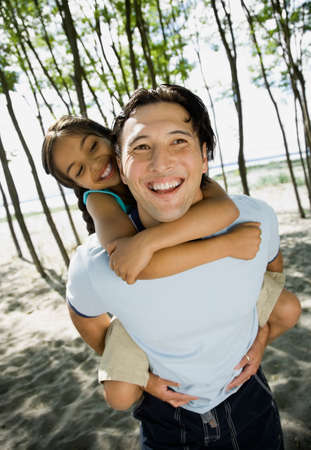 Mixed Race father giving daughter piggyback ride Stock Photo