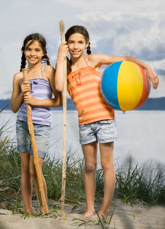 spectating: Mixed Race sisters at beach LANG_EVOIMAGES