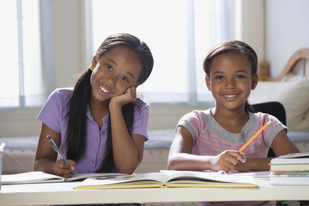 elementary age girls: African American sisters studying