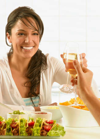 ostentatious: Hispanic woman toasting over food LANG_EVOIMAGES