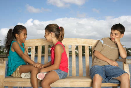 mixed race children: Mixed Race children on bench LANG_EVOIMAGES