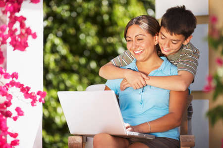 typist: Hispanic mother and son looking at laptop