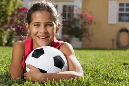 africanamerican: Mixed Race girl holding soccer ball LANG_EVOIMAGES